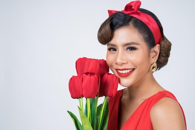 Портрет красивой женщины с букетом красных тюльпанов