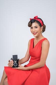 Счастливые руки фотографа женщины моды держа ретро винтажную камеру