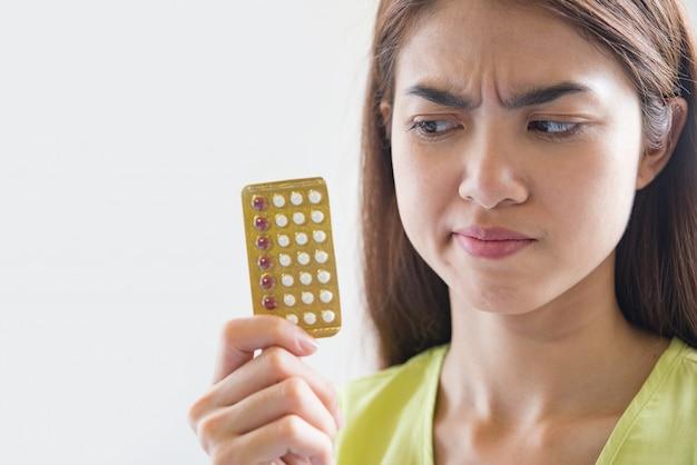 避妊薬のパネルを持つ女性の手が妊娠を防ぐ