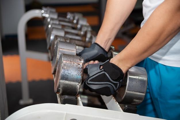 運動のための古い重量のダンベルを拾う両手