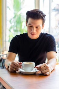 白いカップでホットコーヒーを探している若い男