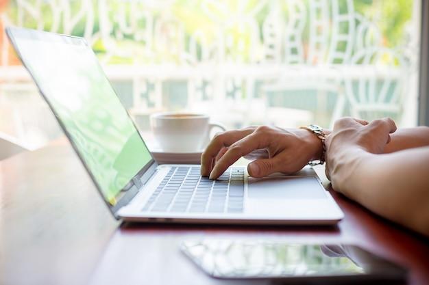 男性の手がカフェでノートパソコンに入力します。
