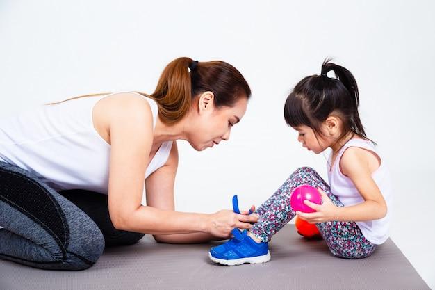 若い母親が靴を履いているかわいい娘を助ける