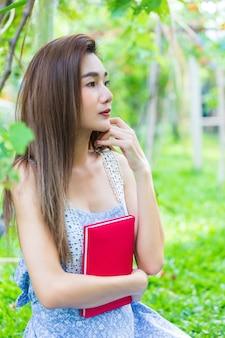 若いきれいな女性は腕に日記を抱擁します。