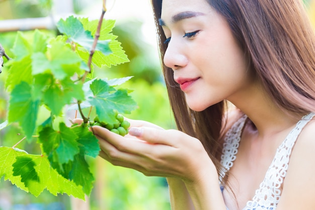 若くてきれいな女性は喜んでブドウの木に感謝
