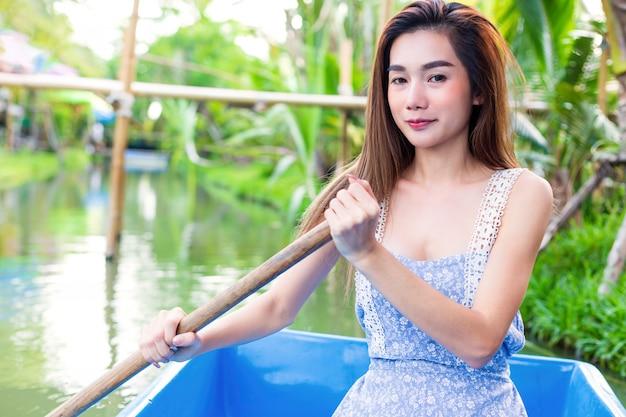 Молодая милая женщина ослабляя гребной лодкой