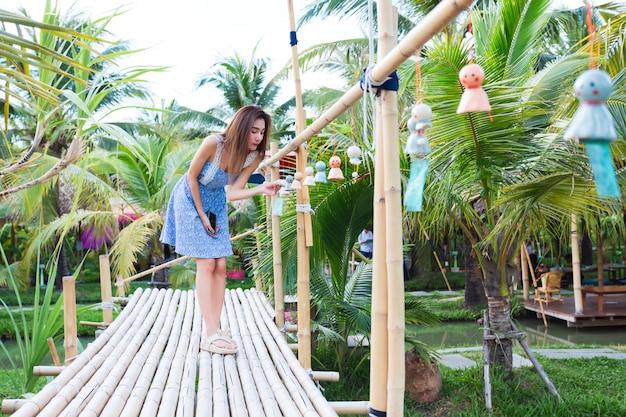 竹の橋の上を歩く若い女性
