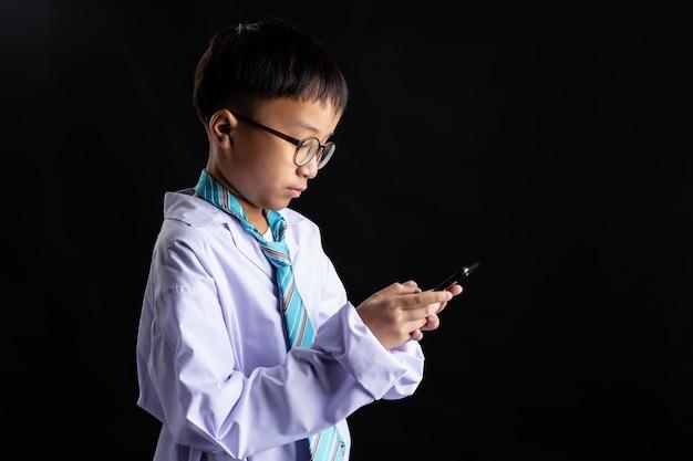 アジアの少年がスマートフォンで大人を模倣