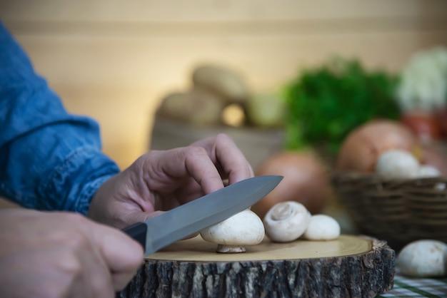 女性は台所で新鮮なシャンピニオンキノコ野菜を調理します