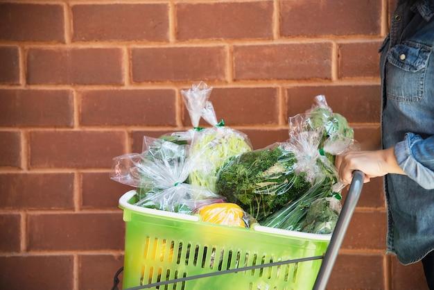 女性はスーパーマーケットで新鮮な野菜を買い物