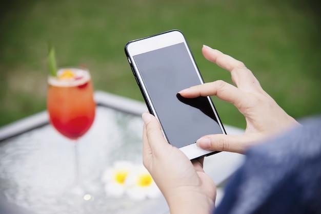 携帯電話を使用して女性は緑豊かな庭園でリラックスします。