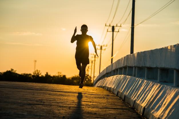 日の出を走っている若いフィットネス男のシルエット