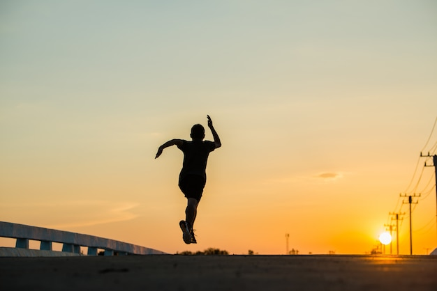 Силуэт молодого человека фитнес работает на рассвете