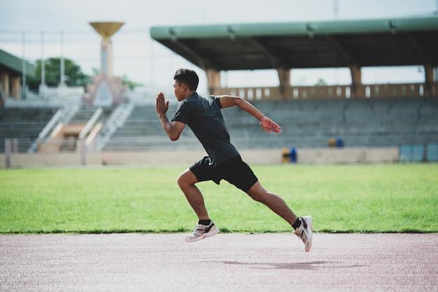 Спортсмен, стоящий на всепогодной беговой дорожке