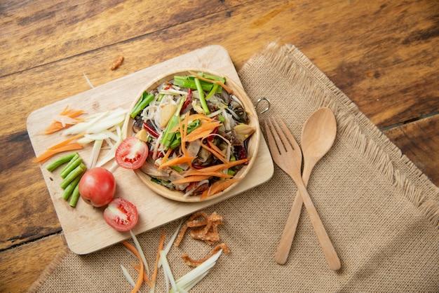 ソムタムタイ、木製の背景にタイのパパイヤサラダ