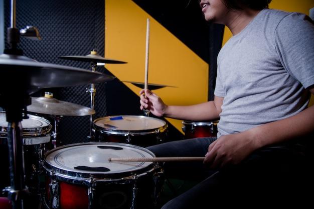 スタジオでドラムセットの音楽を録音する男
