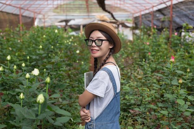 バラ園でタブレットを保持している農業の女性。