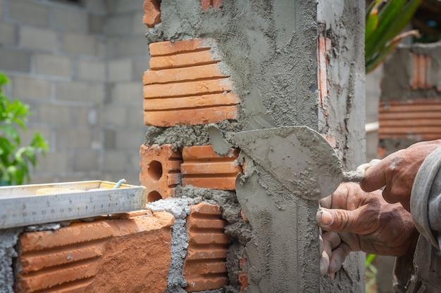 Кладка. строительный рабочий, строительство кирпичной стены.