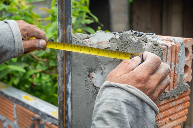 レンガ造り。建設労働者がレンガの壁を構築します。