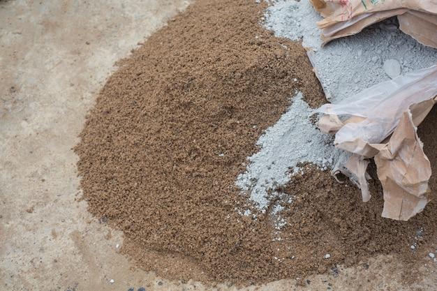 Строительные техники смешивают цемент, камень, песок для строительства.