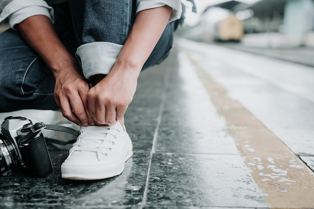 靴ひも、電車の通路、休日、旅行のアイデアに縛られた女性。