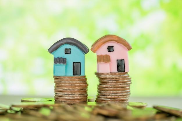 緑のぼかしとコインのスタック上のミニハウス。