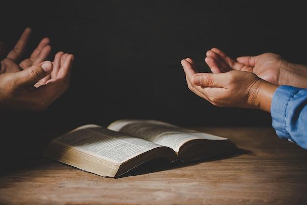 礼拝を祈って手を繋いでいる人々のグループ