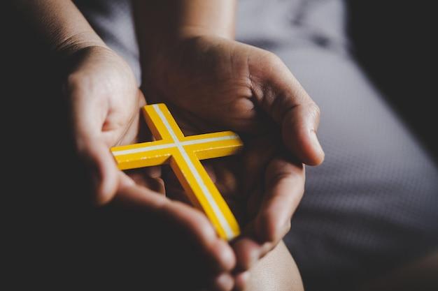 Духовность и религия, женщины в религиозных концепциях руки молятся богу, держа крест символ. монахиня схватила крест в руке.