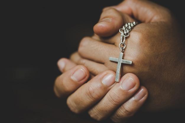 精神性と宗教、宗教概念の女性十字のシンボルを保持しながら神に祈る手。修道女は手に十字架をつかまえました。