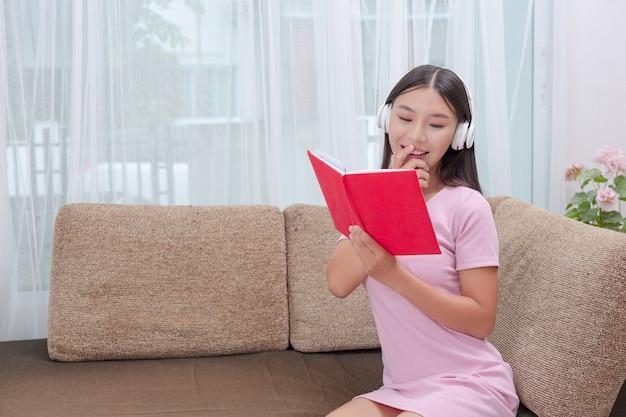 音楽を聴くと本を読むソファに横たわった少女。