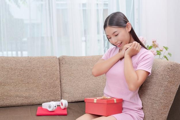 ピンクのドレスで美しい女性、ソファに座って、ギフトボックスを開きます。
