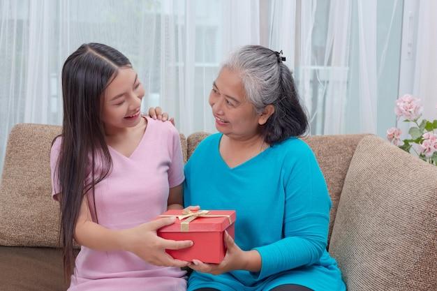 美しい若い女性は母親に贈り物をします。