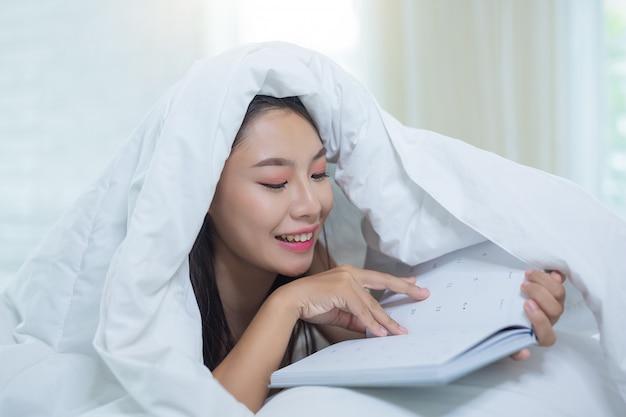 音楽を聞きながら本を読んでベッドに横たわっている少女。