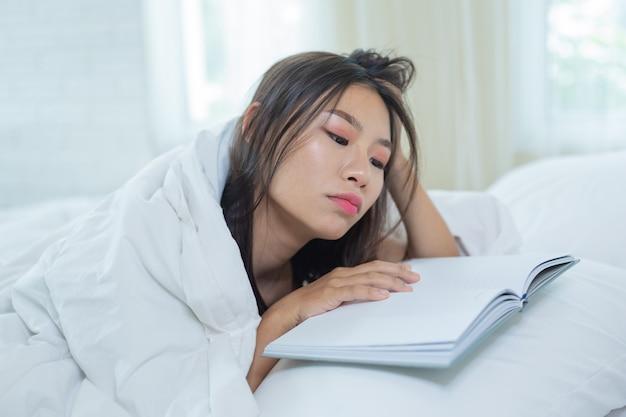 Девушка лежа в кровати слушая к музыке и читая книги.