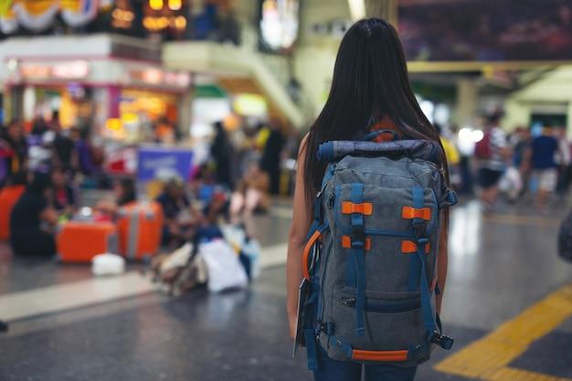 女性は地図上で駅まで旅行することを楽しんでいます。