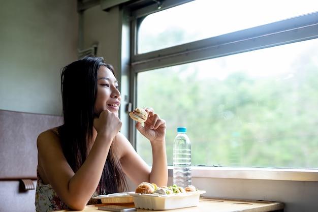 女性は電車、休日、旅行のアイデアで朝食を食べます。