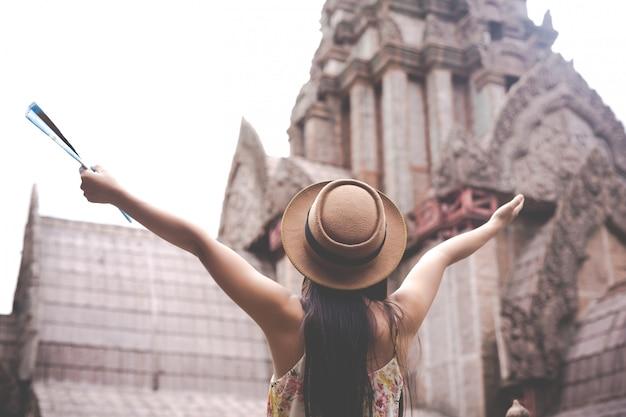Девушка держит туристическую карту в старом городе.