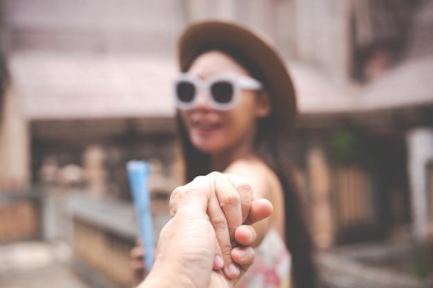 男性と女性が手をつないで旅行します。