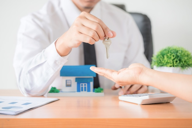 Агент по продаже недвижимости передает ключ от квартиры новому владельцу