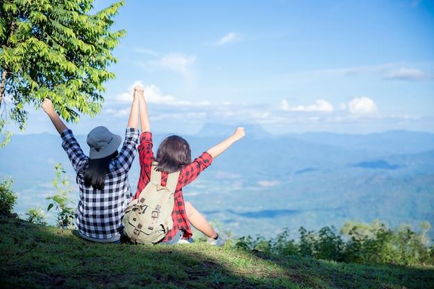 Путешественники, молодые женщины, смотрят на удивительные горы и леса, идеи путешествий странствий,