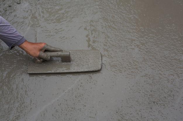 建設技術者は、建設のためにセメント、石、砂を混ぜています。