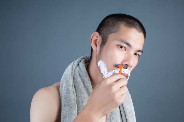 灰色の顔を剃るハンサムな男を剃る