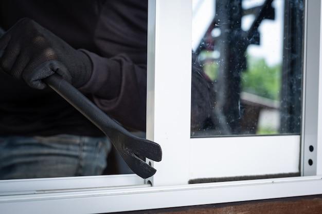 泥棒は黒い帽子を着用し、窓をこじ開け、物を盗みます。
