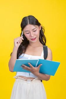 Красивые студентки держат блокноты и ручки
