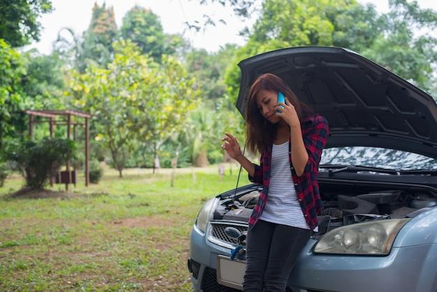 若い女性が車を壊し、彼女は緊急サービスを呼んでいます。