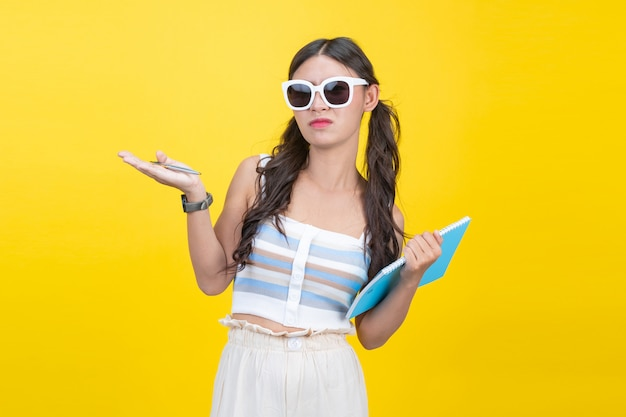 美しい女子学生がノートとペンを保持