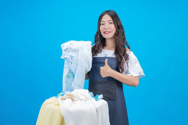 Красивая женщина, держащая ткань, подготовленную для стирки на синем