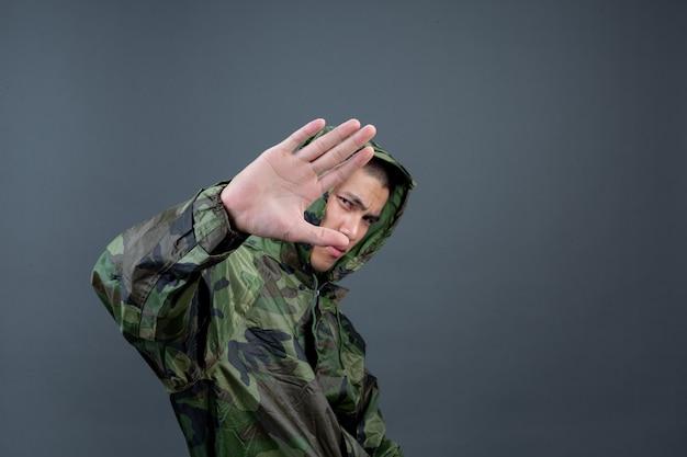 若い男はカモフラージュのレインコートを着ており、さまざまなジェスチャーを示しています。