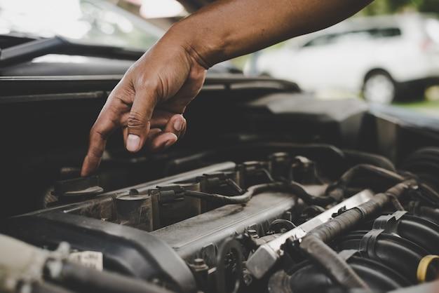 車のエンジンを調べている男。