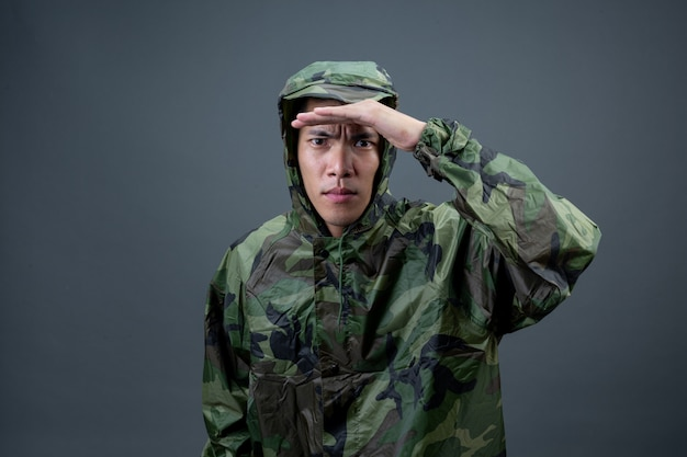 Молодой человек носит камуфляжный плащ и показывает разные жесты.